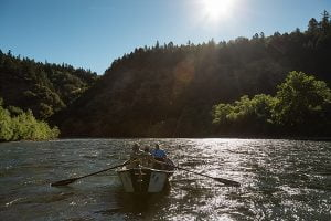 Guide rows fishing boat on the Rogue River